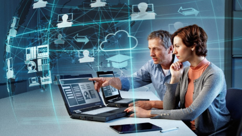 Man and woman at computers with digital graphics