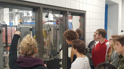 Group of students at the museum looking at a robot part behind the glass